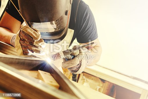 Male in face mask, protective gloves welds with argon-arc welding. Welder makes weld seam on metal frame. Worker dressed in t-shirt and overalls.