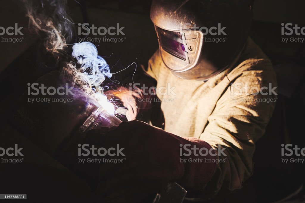 Male in face mask, protective gloves welds with welding. Welder makes...