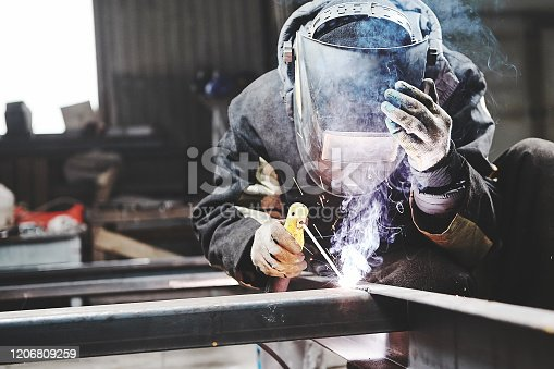 istock Male in face mask welds with welding 1206809259