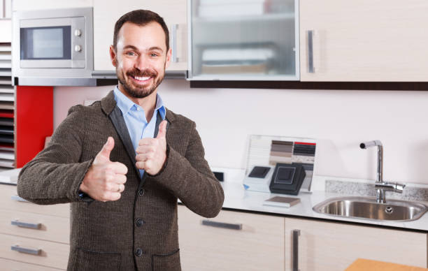 Male in kitchen furniture salon Portrait of positive male standing in salon of kitchen furniture approbation stock pictures, royalty-free photos & images