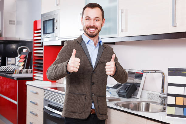 Male in kitchen furniture salon Portrait of happy male standing in shop of kitchen furniture approbation stock pictures, royalty-free photos & images