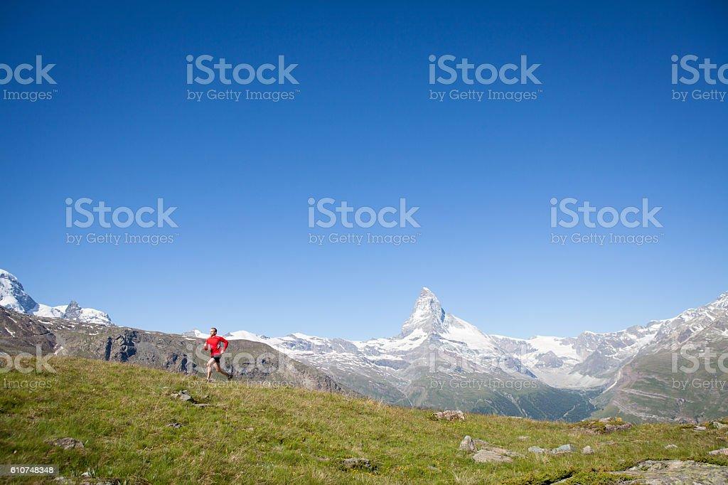 Male in red mountain running near the Matterhorn stock photo