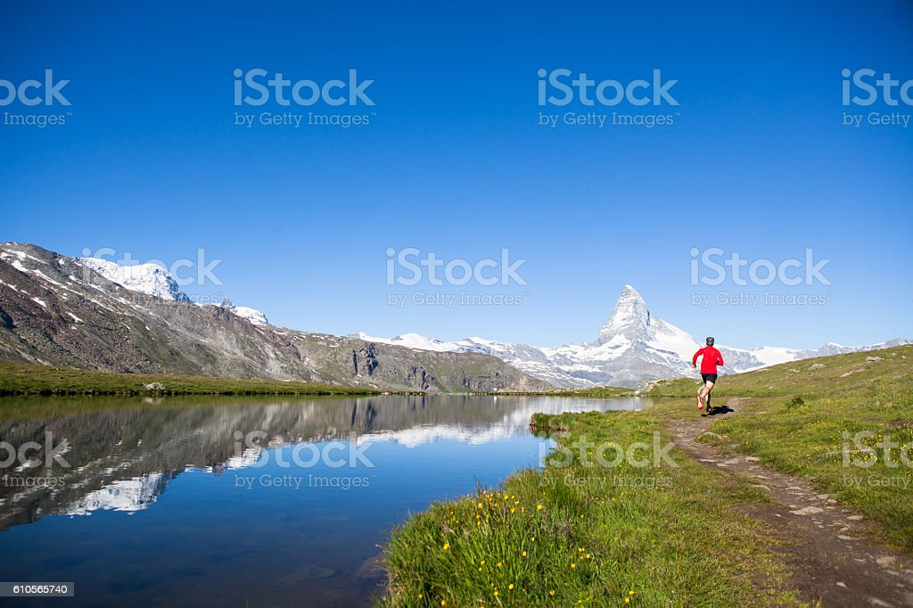 Male in red running in the mountains stock photo