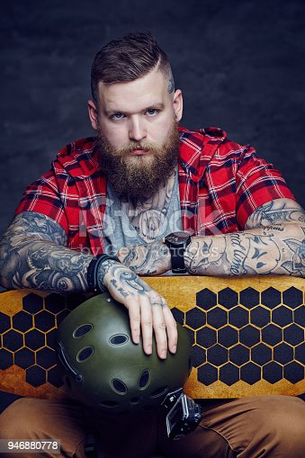 istock Male in red shirt posing with longboard in studio. 946880778