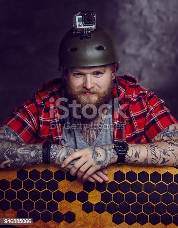 istock Male in red shirt posing with longboard in studio. 946885066