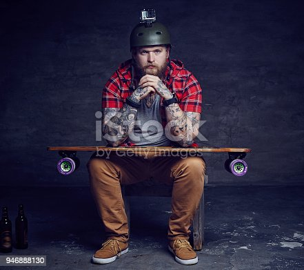 istock Male in red shirt posing with longboard in studio. 946888130