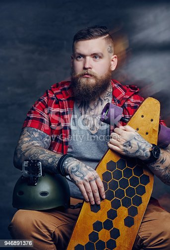 istock Male in red shirt posing with longboard in studio. 946891376
