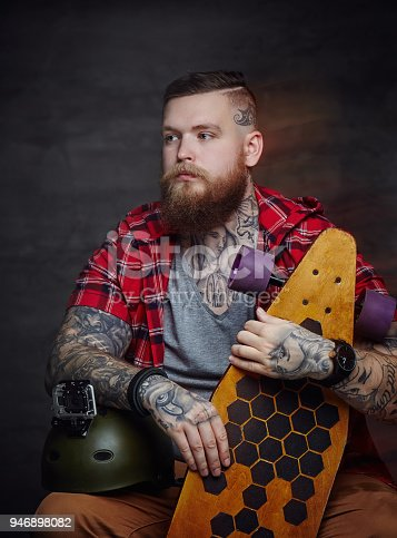 istock Male in red shirt posing with longboard in studio. 946898082