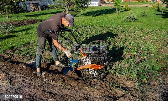 Male in the spring plows the earth in working clothes with a motoblock, walk-behind tractor
