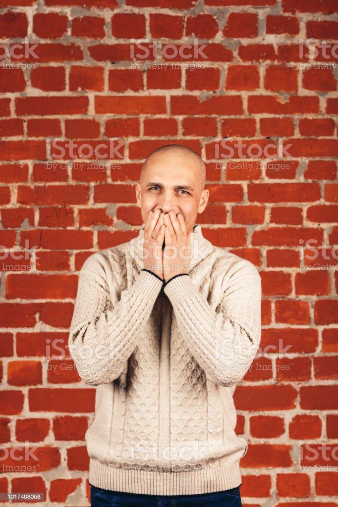 homem de camisola branca fecha sua boca em backgraund da parede de tijolo. Copie o espaço. - foto de acervo