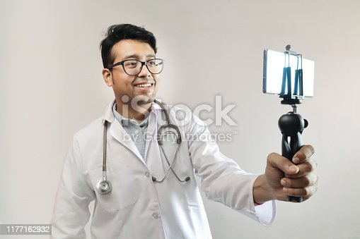 male indian doctor in white coat and stethoscope clicking selfie with a mobile tripod and futuristic concept cameraphone