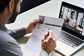 istock Male indian hr, recruiter or employer holding cv having online virtual job interview meeting with african candidate on video call. Distance remote recruitment conference chat. Over shoulder view. 1307598870
