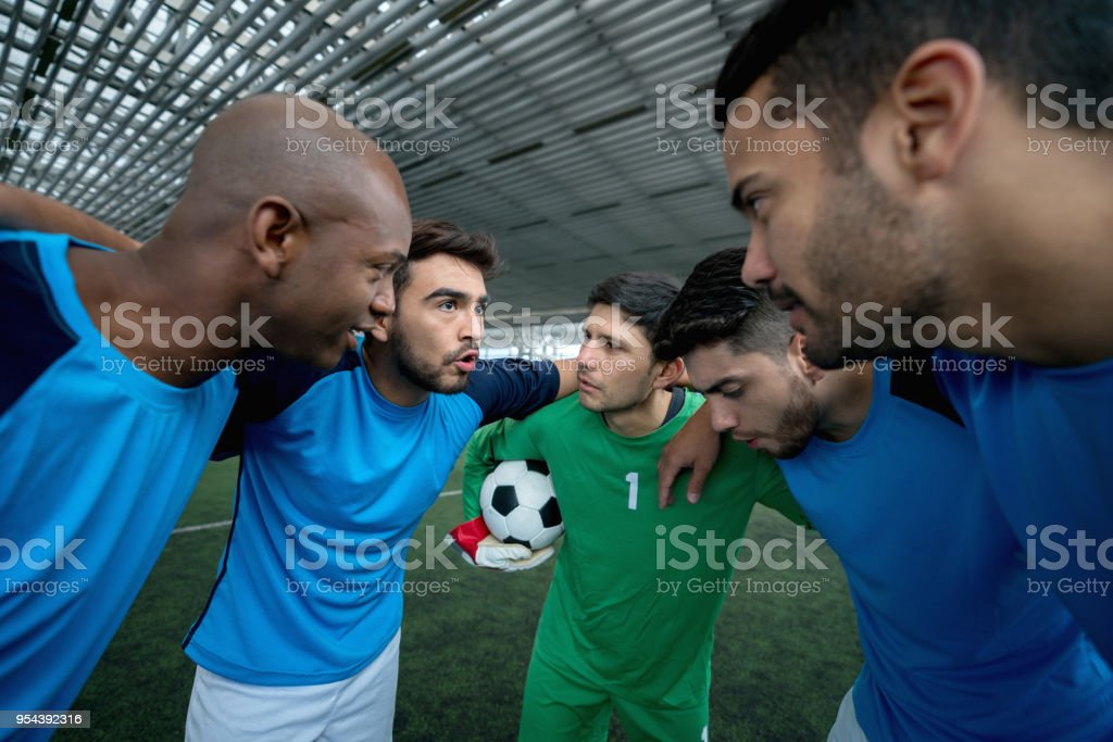 Male indoor soccer team on a huddle talking before starting the game...