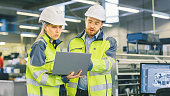istock Male Industrial Worker and Female Chief Mechanical Engineer in Walk Through Manufacturing Plant while Discuss Factory's New Project and Using Laptop. Facility Has Working Machinery. 1135159596