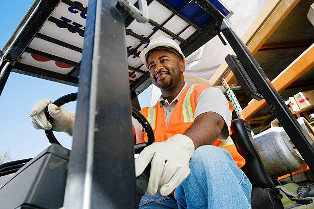 Male Industrial Worker Driving Forklift At Workplace stock photo