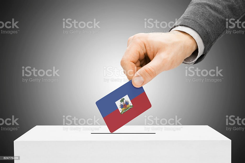 Male inserting flag into ballot box - Haiti stock photo
