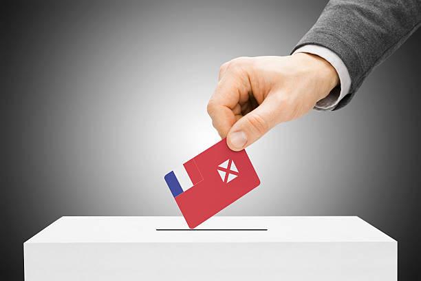 Male inserting flag into ballot box - Wallis and Futuna stock photo