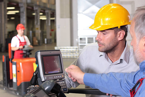 male inspector and fork lift operator working with control panel stock photo