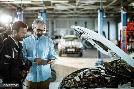 1137474295 istock photo Male inspector using touchpad with repairman in auto repair shop. 1164677045