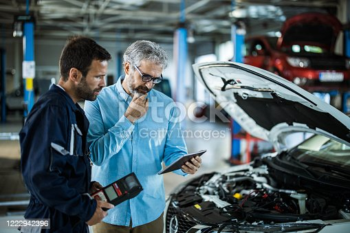 1137474295 istock photo Male inspector using touchpad with repairman in auto repair shop. 1222942396