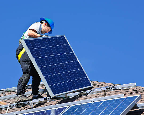Male installing solar panel on roof stock photo