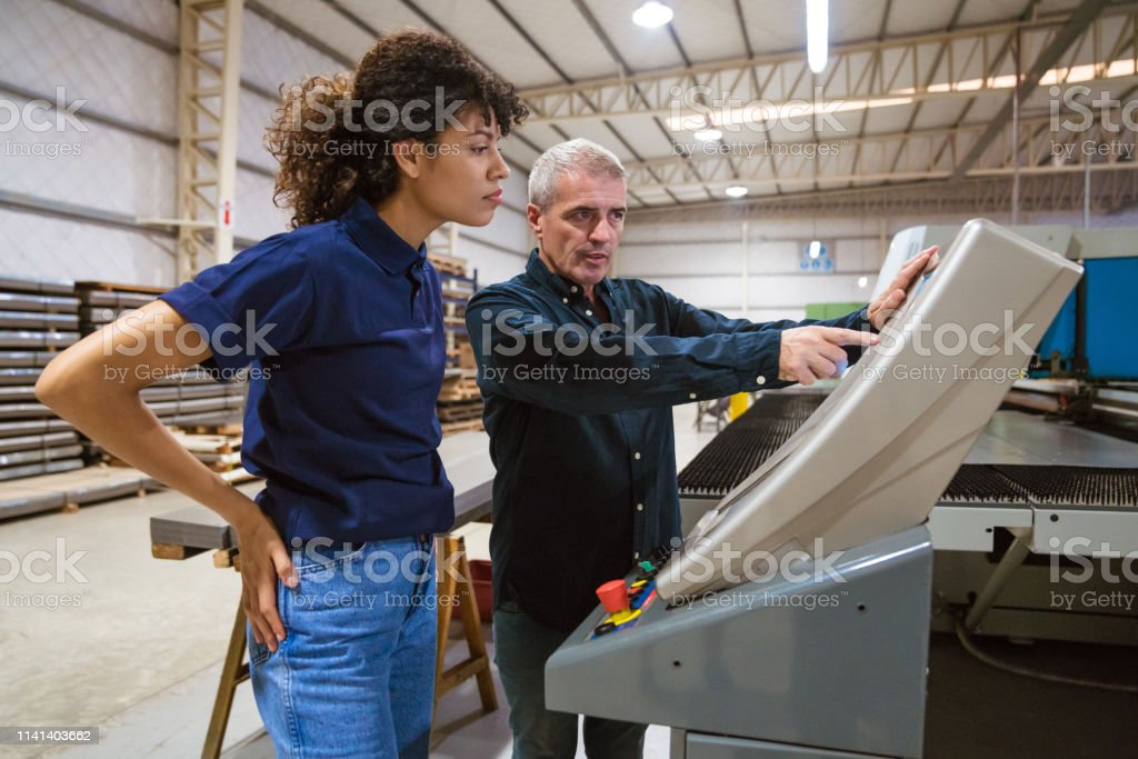 Male instructor explaining apprentice in factory Mature male engineer explaining female trainee in industry. Instructor is discussing with apprentice over puller machine. They are working in factory. 30-34 Years Stock Photo