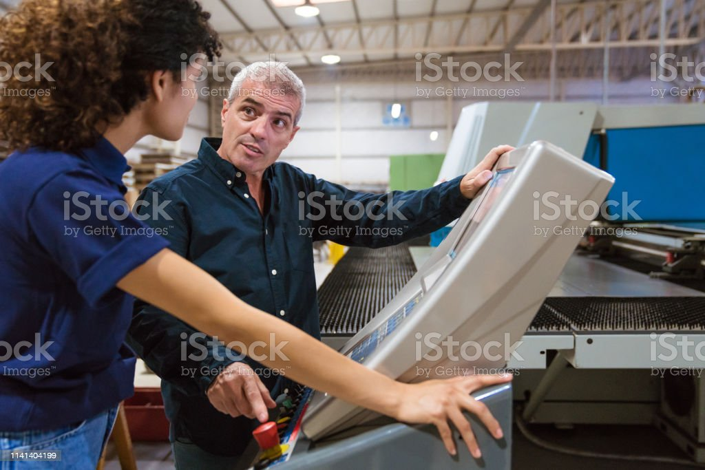 Male instructor explaining trainee in factory Male engineer discussing with female apprentice over puller machine. Instructor is teaching young trainee in industry. They are working in factory. 30-34 Years Stock Photo
