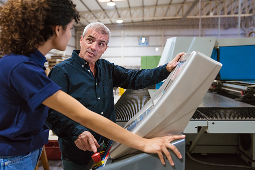 Male Instructor Explaining Trainee In Factory Stock Photo - Download Image Now