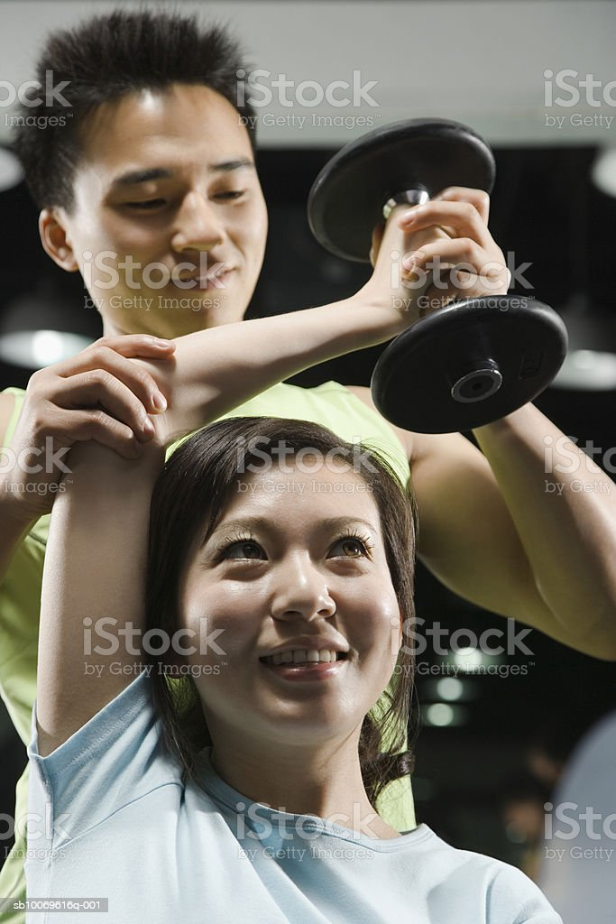 Male instructor giving weight training to woman in gym, close-up royalty-free stock photo