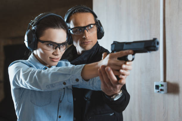 male instructor helping attractive female customer holding gun stock photo