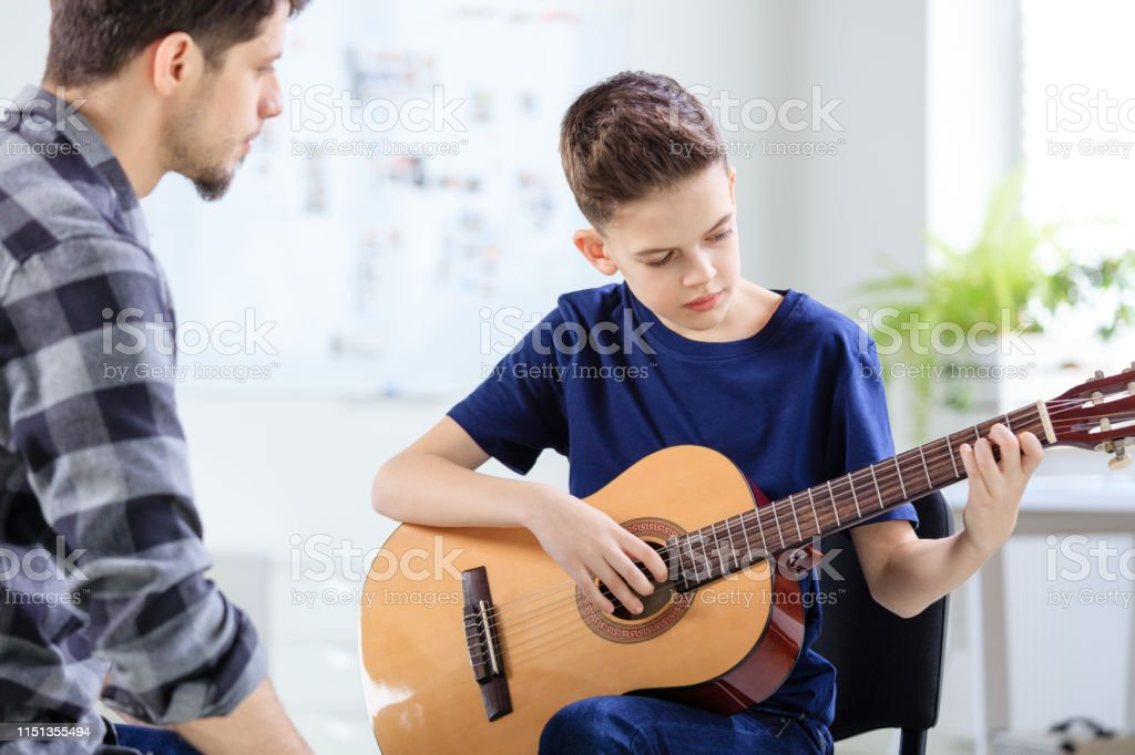 Male instructor looking at boy playing guitar Instructor looking at boy playing guitar in training class. Confident student is learning string instrument in classroom. They are at conservatory. 12-13 Years Stock Photo
