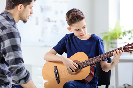 Male Instructor Looking At Boy Playing Guitar Stock Photo - Download Image Now
