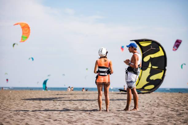 männliche lehrer im gespräch mit einer frau vor dem kitesurfen im sommertag. - kitesurfen lernen stock-fotos und bilder