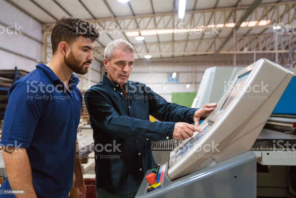 Male instructor teaching apprentice in factory Mature male engineer explaining trainee in factory. Instructor is discussing with apprentice over puller machine. They are working in industry. 20-24 Years Stock Photo