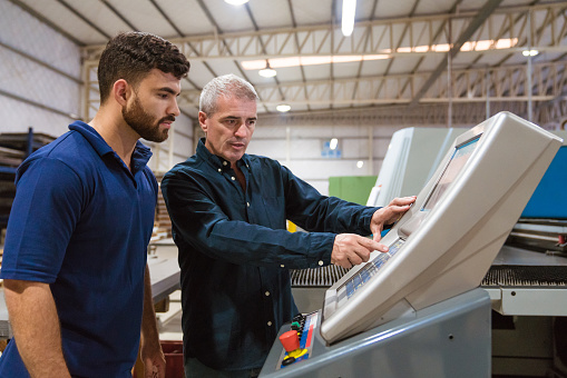 Male Instructor Teaching Apprentice In Factory Stock Photo - Download Image Now