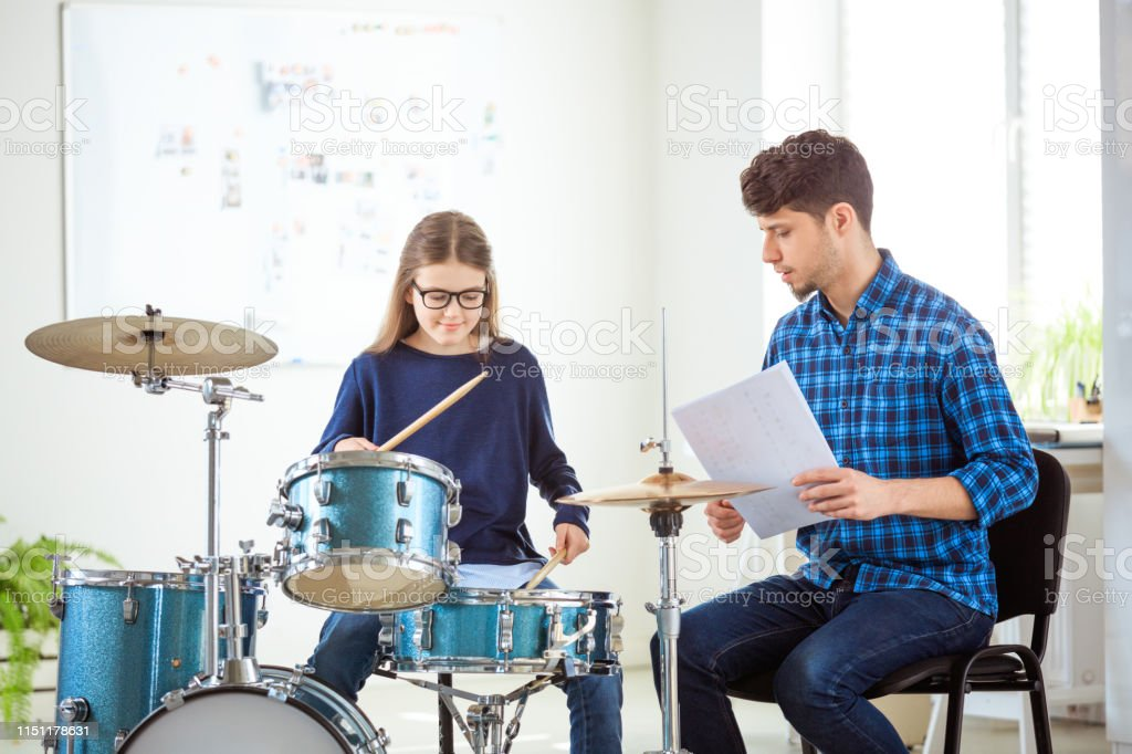Male instructor teaching female drummer in class Mid adult trainer with sheet instructing pre-adolescent student. Female drummer is practicing with music teacher. They are sitting in conservatory. 10-11 Years Stock Photo