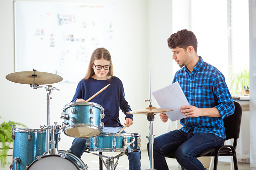 Male Instructor Teaching Female Drummer In Class Stock Photo - Download Image Now