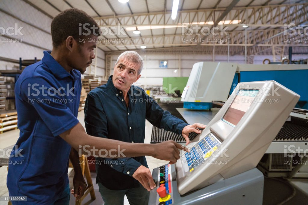 Male instructor teaching trainee in factory Mature male instructor teaching trainee in industry. Engineers are discussing over puller machine. They are working in factory. 25-29 Years Stock Photo