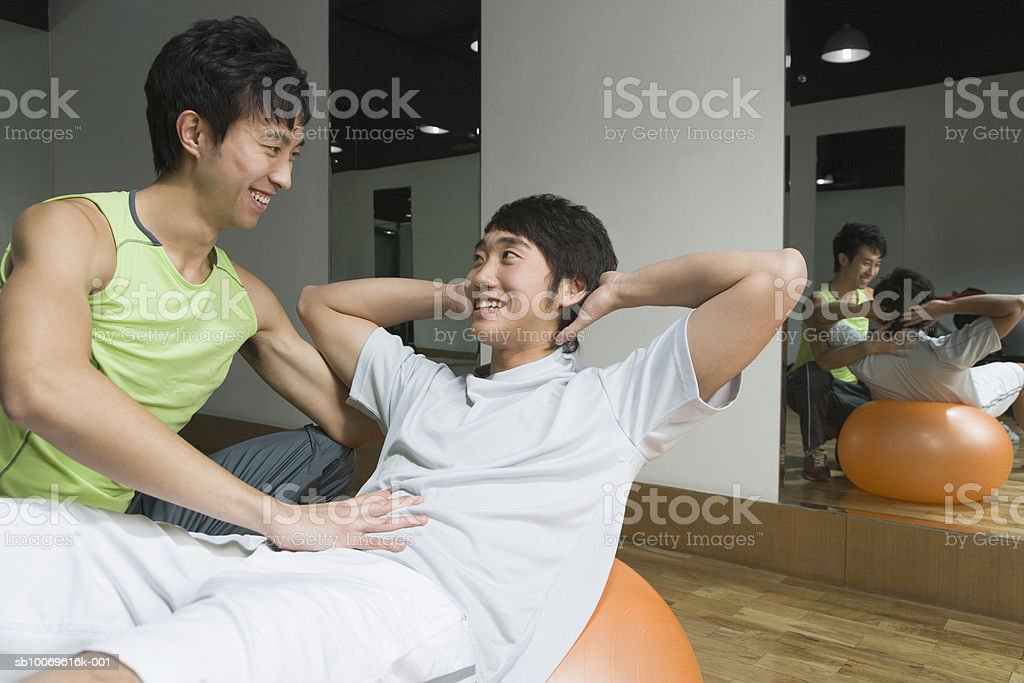 Male instructor training man on exercise ball, smiling royalty-free 스톡 사진