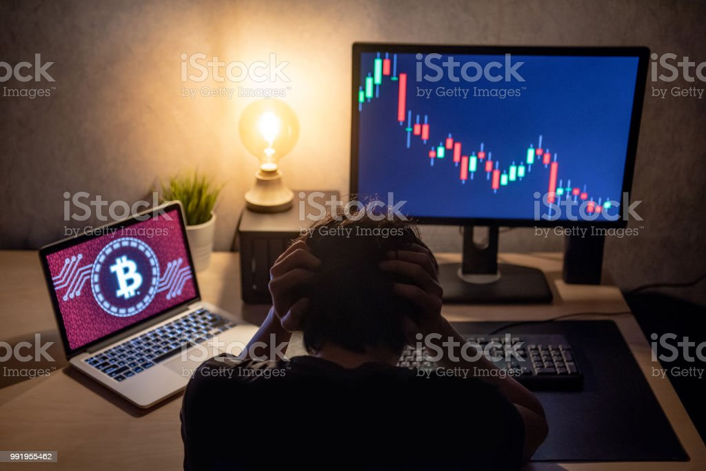 Male Investor feeling stressed and frustrated due to bitcoin crisis with candlestick graph price down on monitor screen. Bitcoin cryptocurrency digital money crisis concept stock photo