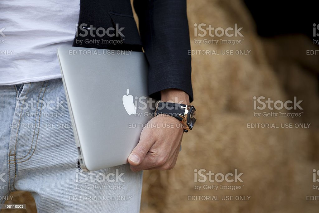 male is holding MacBook Air stock photo
