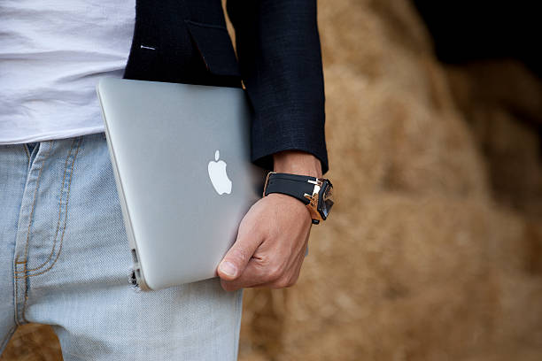 Hombre agarra MacBook Air - foto de stock