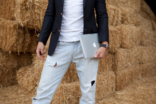 male is holding MacBook Air