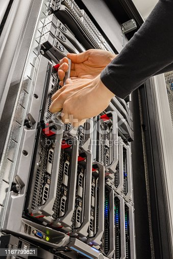istock Male IT Consultant Removing Blade Server From Rack in Datacenter 1167799821