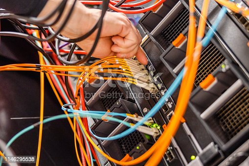 istock Male IT Engineer Plugging High Speed Fiber Cable In Network Switch 1146295538