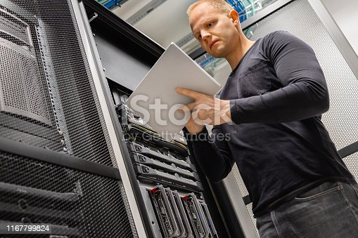 istock Male IT Engineer Using Tablet In Datacenter to Monitor Network and Servers 1167799824