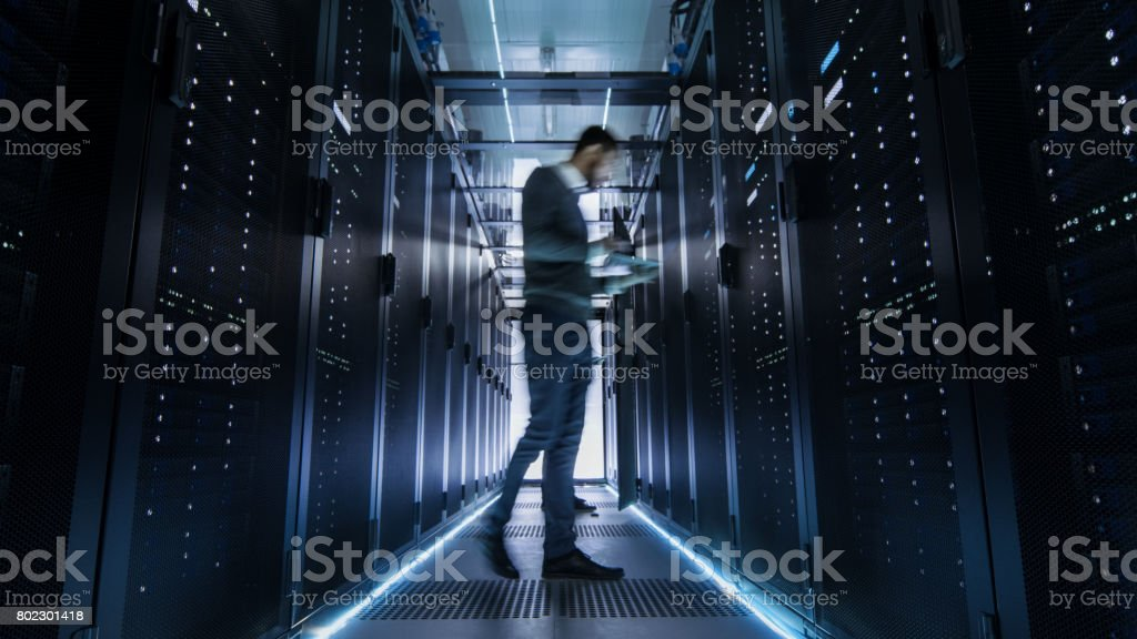Male IT Engineer Walking and Working in Data Center Corridor. She is Holding Tablet Computer. She is Blurred in Motion. stock photo