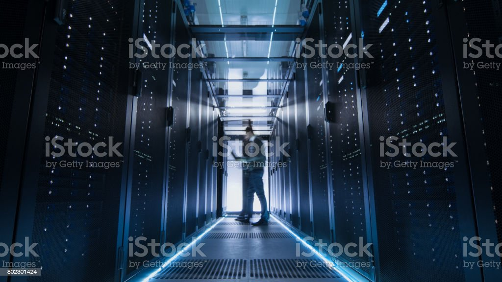 Male IT Engineer Walking and Working in Data Center Corridor. She is Holding Tablet Computer. He is Blurred in Motion. stock photo