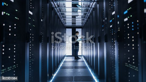 899720520istockphoto Male IT Engineer Works on a Laptop at the end of a Corridor in a Big Data Center. Rows of Rack Servers are Seen. 802301584