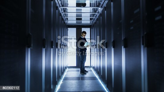 802303672istockphoto Male IT Engineer Works on a Laptop at the end of a Corridor in a Big Data Center. Rows of Rack Servers are Seen. 802302112